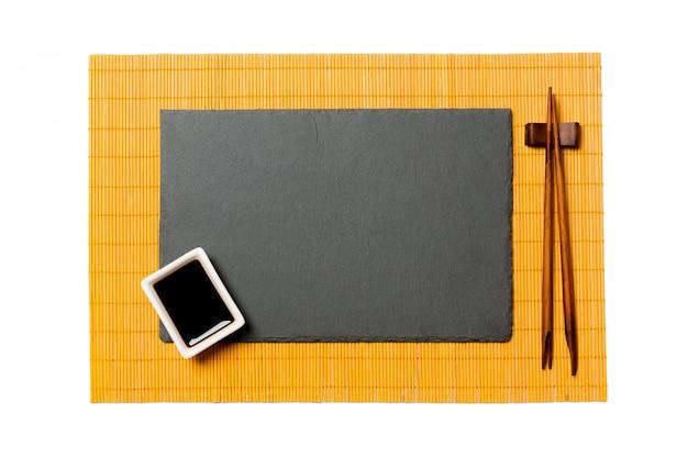 Leere rechteckige schwarze schieferplatte mit essstäbchen für sushi und sojasoße auf gelbem bambusmattenhintergrund