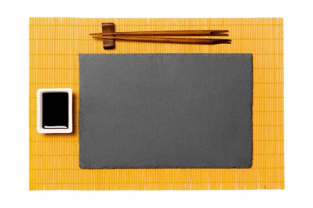 Leere rechteckige schwarze schieferplatte mit essstäbchen für sushi und sojasoße auf gelber bambusmatte. draufsicht mit exemplar