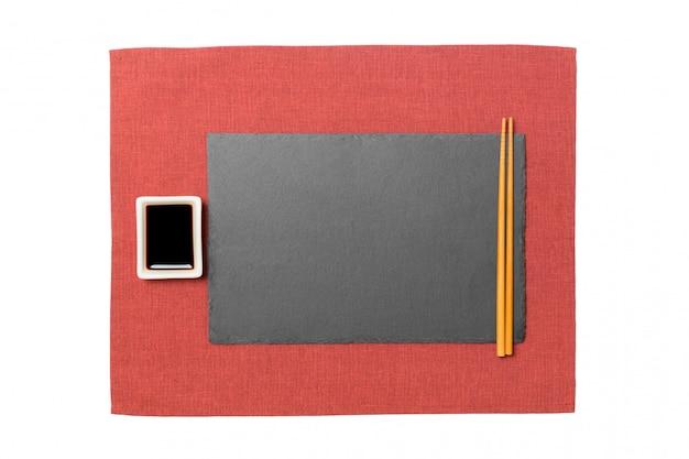 Leere rechteckige schwarze schieferplatte mit essstäbchen für sushi und sojasoße auf rotem serviettenhintergrund