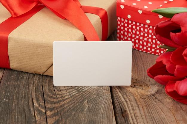 Leere rechteckige weiße papiergrußkarte, ein strauß roter tulpen und verpackter geschenke