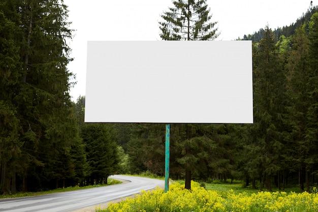 Leere riesige plakatwand, die nahe straße auf dem weg zu bergen steht und viele immergrüne bäume herum hat