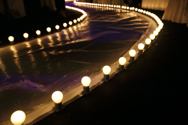 Leere rollbahn-modeschau mit glühender beleuchtung des balls entlang wegweise mit weißem plastikboden in der dunkelheit