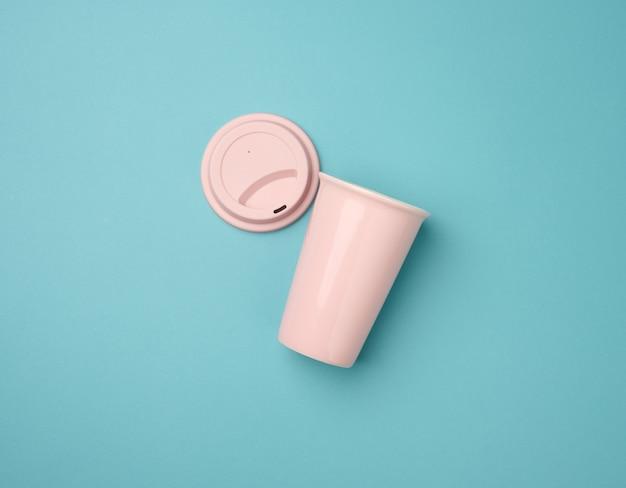 Leere rosa keramiktasse mit gummideckel für cappuccino und kaffee auf blauem hintergrund