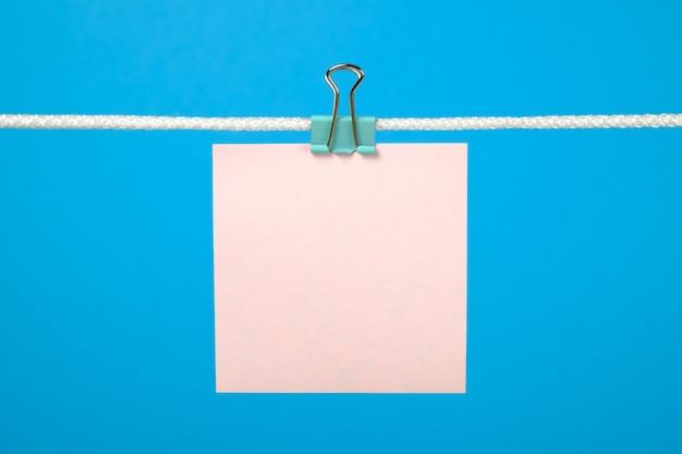 Leere rosa papierblätter hängen an schnur