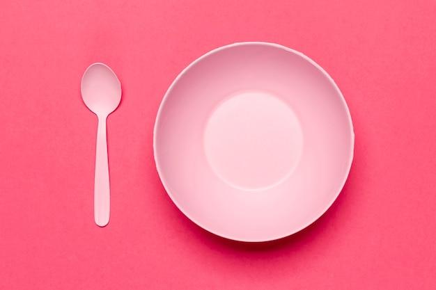 Leere rosa schüssel und löffel der draufsicht