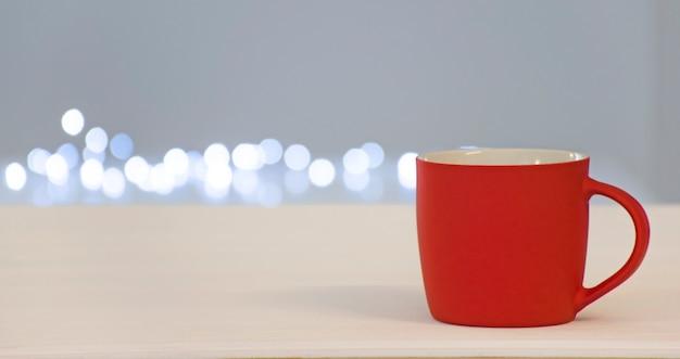 Leere rote tasse mit freiem platz für text oder emblem mit eingeschalteten bokeh-lichtern