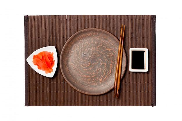 Leere runde braune platte mit essstäbchen