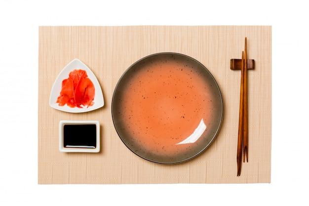 Leere runde braune platte mit essstäbchensushi, ingwer und sojasoße auf brauner sushimatte