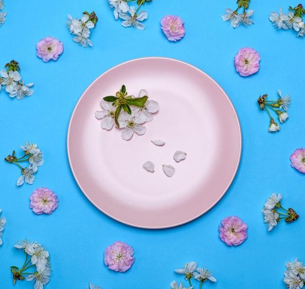 Leere runde keramische rosa platte auf einem blau inmitten der blühenden knospen