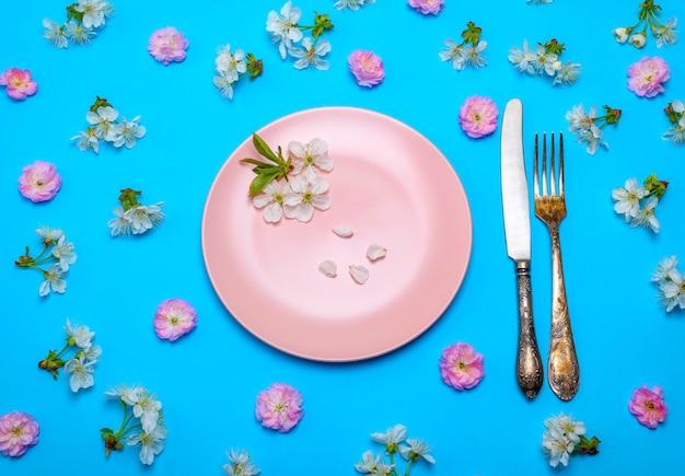 Leere runde rosa keramikplatte und ein weinlesemesser mit einer gabel