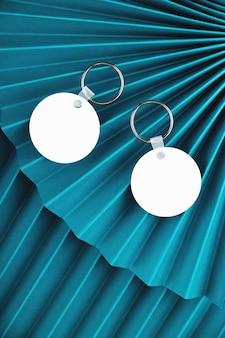 Leere runde schlüsselanhänger-modelle auf blauen papierfans