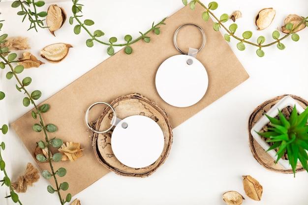 Leere runde schlüsselanhänger-modelle in der nähe natürlicher dekorationen