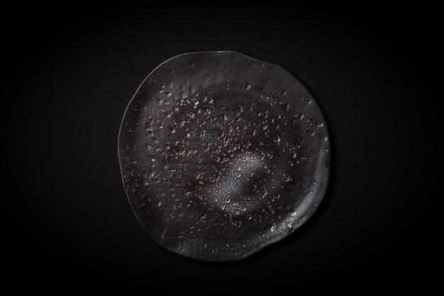 Leere runde schwarze gealterte keramische platte auf dunklem hintergrund