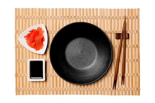 Leere runde schwarze platte mit essstäbchen
