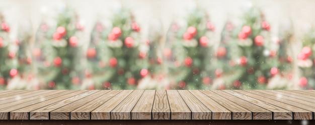 Leere rustikale hölzerne plankentischplatte mit rotem dekorball und abstraktem des abstrakten unschärfeweihnachtsbaums