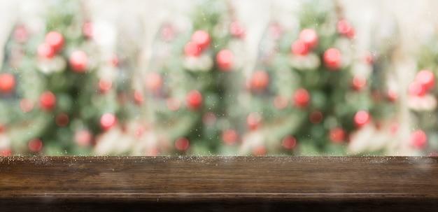 Leere rustikale hölzerne tabelle mit unschärfeweihnachtsbaum
