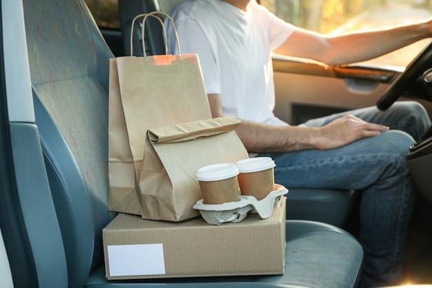 Leere schachtel, kaffeetassen, papierverpackungen und kurier im auto. lieferung