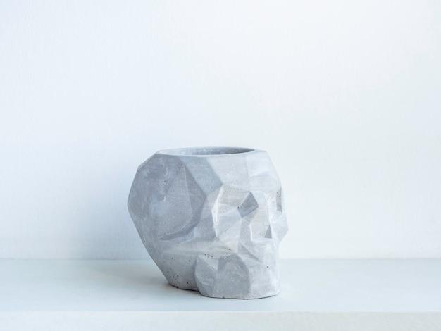 Leere schädelform beton blumentopf auf weißem holzregal isoliert auf weißer wand. kleine moderne diy-zementpflanzer trendige dekoration.