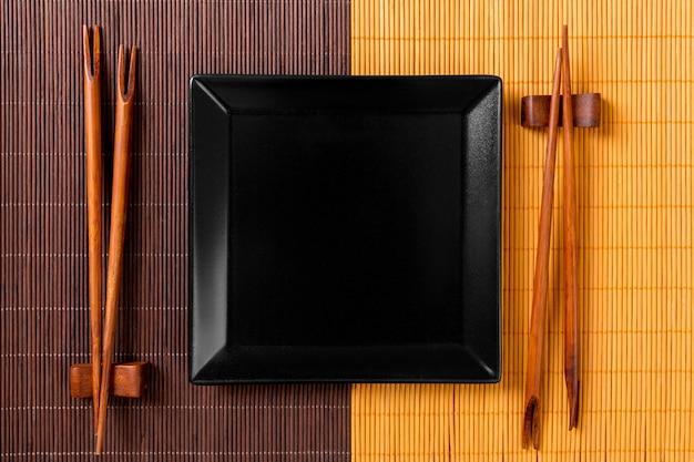 Leere schieferplatte des schwarzen quadrats mit essstäbchen für sushi auf holz