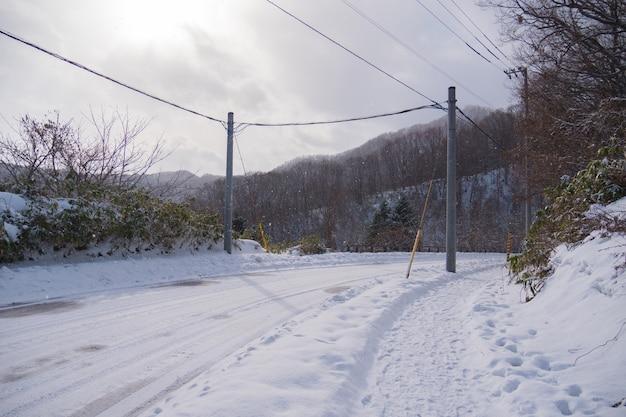 Leere schneebedeckte straße berg und baum im winter