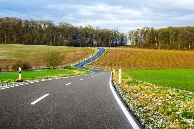Leere schwarze asphaltstraße zwischen grünen feldern