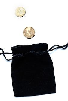 Leere schwarze geldtasche auf weißem hintergrund und zwei euro-cent-münzen, konzept der einsparungen, lagerung, wachstum, akkumulation, rückgang.