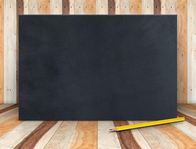 Leere schwarze gewebeplakatleinwand mit gelbem bleistift am hölzernen plankenraum