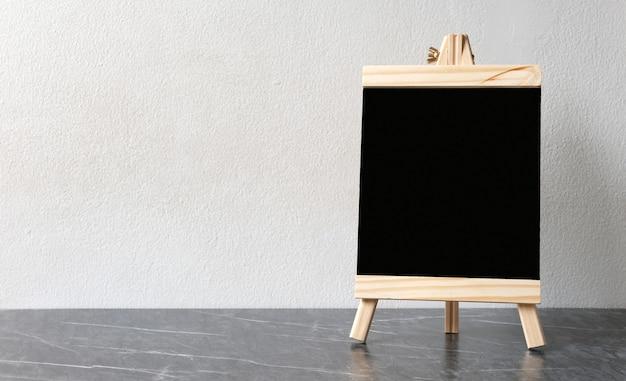 Leere schwarze hölzerne menütafel, tafel, stehend über weißer zementwand
