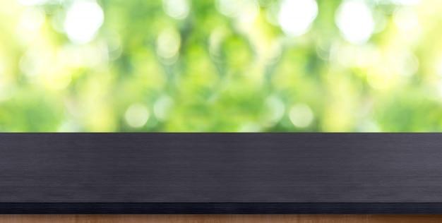 Leere schwarze hölzerne tischplatte mit unschärfebaum im park mit bokeh