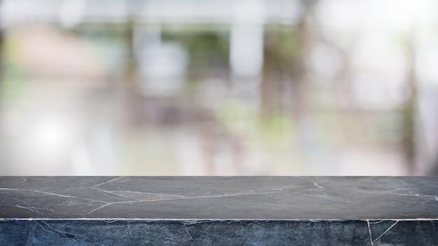 Leere schwarze marmorstein-tischplatte und verwischen glasfensterinnenrestauranthintergrund