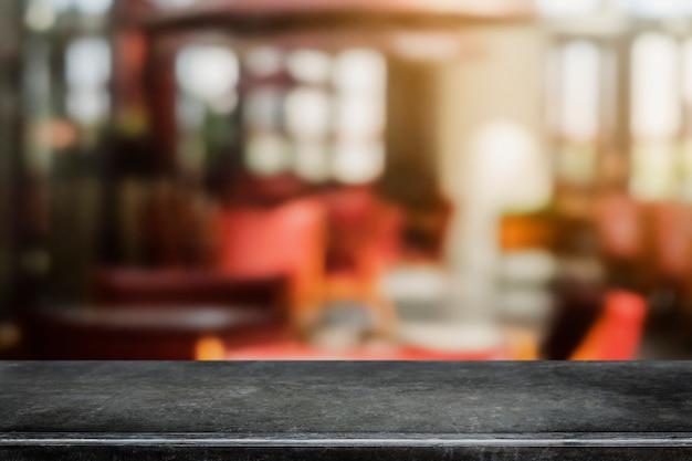 Leere schwarze marmorsteintischplatte und unscharfer kaffeestube- und restauranthintergrund.