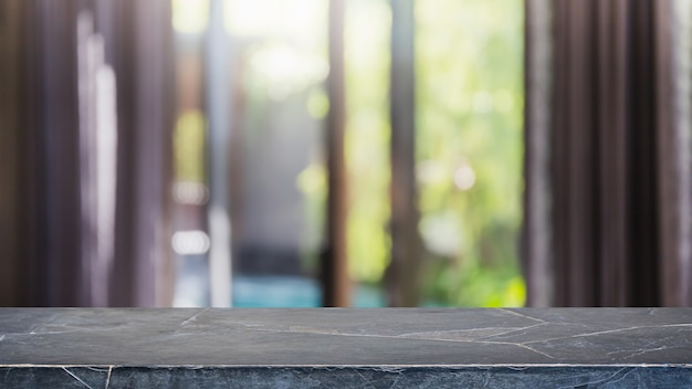 Leere schwarze marmorsteintischplatte und verschwommenes interieur mit vorhangfensterhintergrund. - kann für die anzeige oder montage ihrer produkte verwendet werden.