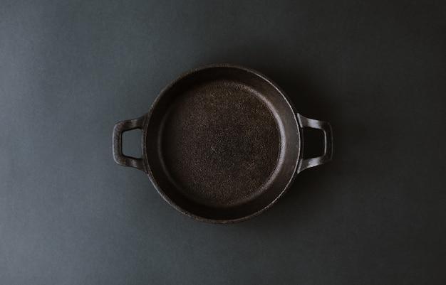 Leere schwarze metallplatte auf einem schwarzen tisch.