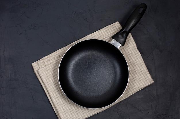 Leere schwarze pfanne mit küchentuch auf schwarzem tisch