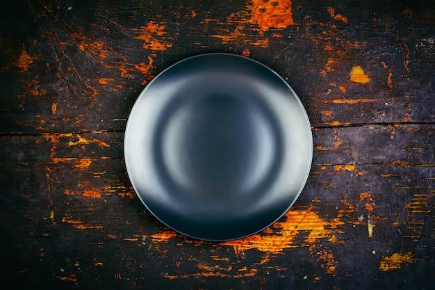Leere schwarze platte auf einer hölzernen vintage-schwarz-grunge-hintergrund-draufsicht