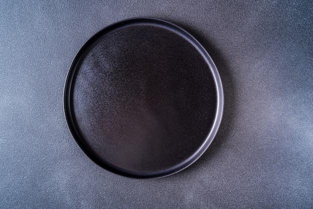 Leere schwarze platte über schwarzer tischoberansicht, kopierraum.