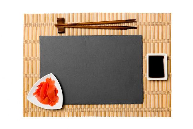 Leere schwarze schieferplatte mit essstäbchen für sushi