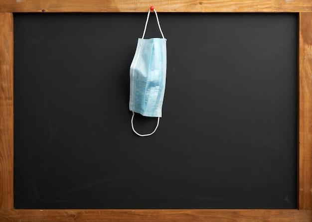 Leere schwarze schultafel, eine medizinische einwegmaske, die an einem roten knopf hängt