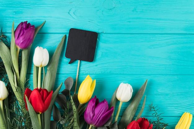 Leere schwarze sprachstütze mit bunten tulpen auf hölzernem hintergrund des türkises