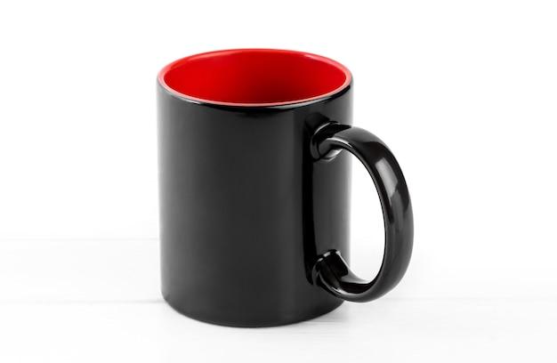 Leere schwarze tasse mit rot auf weißem hintergrund