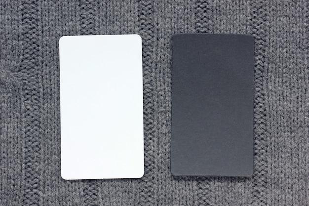 Leere schwarzweiss-karte auf einem gestrickten grauen hintergrund, draufsicht. modell, szenenschöpfer.