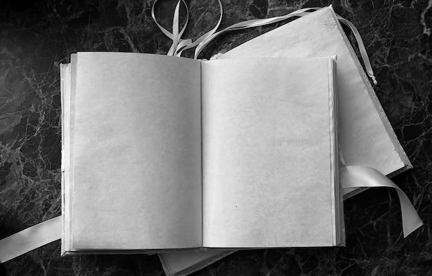 Leere seiten öffneten vintage-buch auf grüner marmor-arbeitsplatte