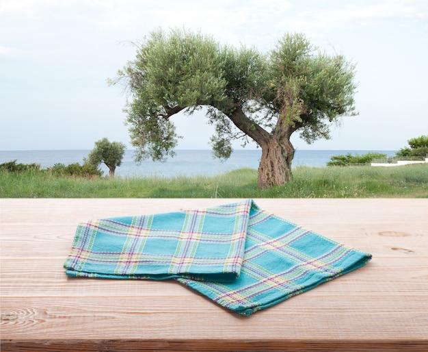 Leere serviette auf holzschreibtisch. sommermeerlandschaft.