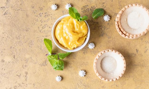 Leere shortbread-törtchen lemon curd mini baiser und minze prozess machen dessert fokus
