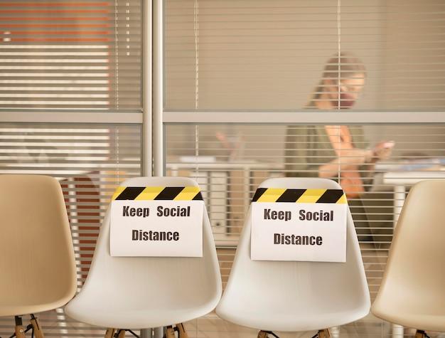 Leere sitze mit sozialem distanzzeichen bei der arbeit