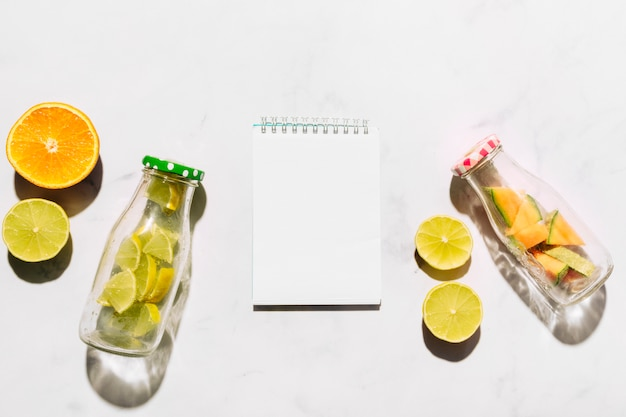 Leere sketchbook kalk orange und glasflaschen mit geschnittenen zitrusfrüchten