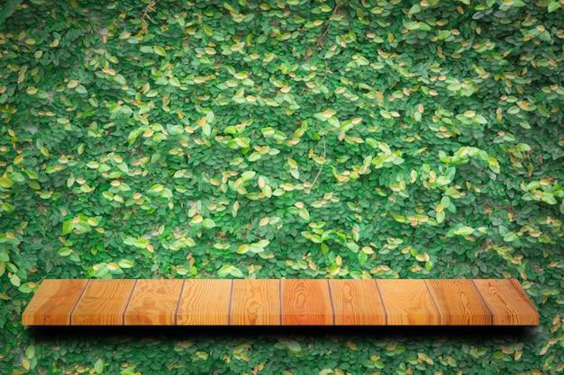Leere spitze der hölzernen tabelle mit grünen blättern