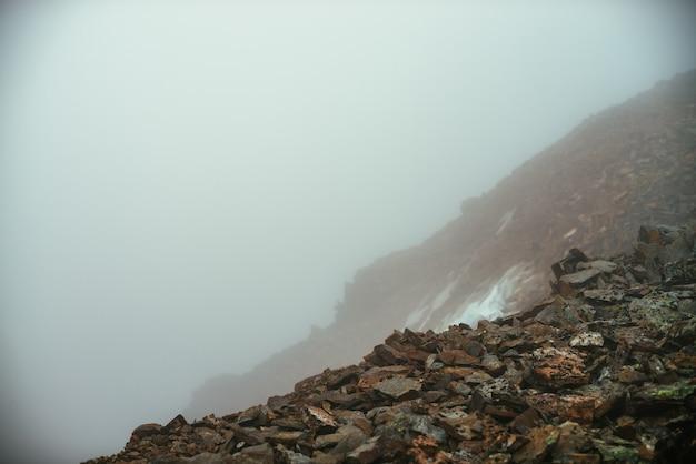 Leere steinwüste in der nähe des abgrunds im dichten nebel. null sichtbarkeit in den bergen. abgrund im dichten nebel im hochland. minimalistischer naturhintergrund. nebelige berglandschaft. flechten auf scharfen steinen.