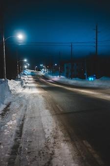 Leere straße mit schnee bei noght