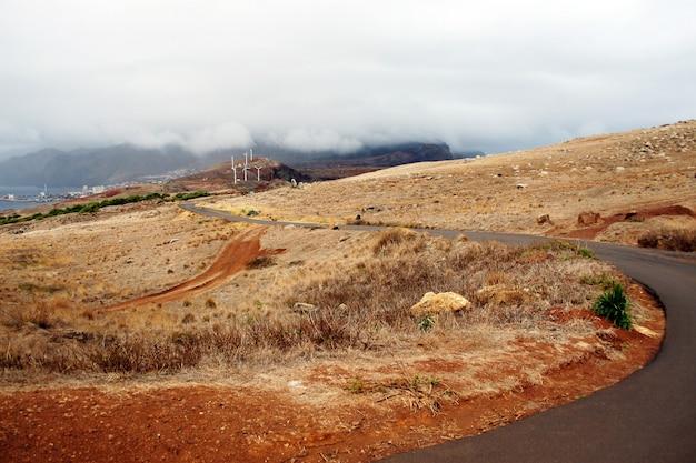 Leere straße, terra-boden, bewölkter himmel und windmühlen. madeira, portugal-landschaft. trend zu öko und erneuerbaren energiequellen